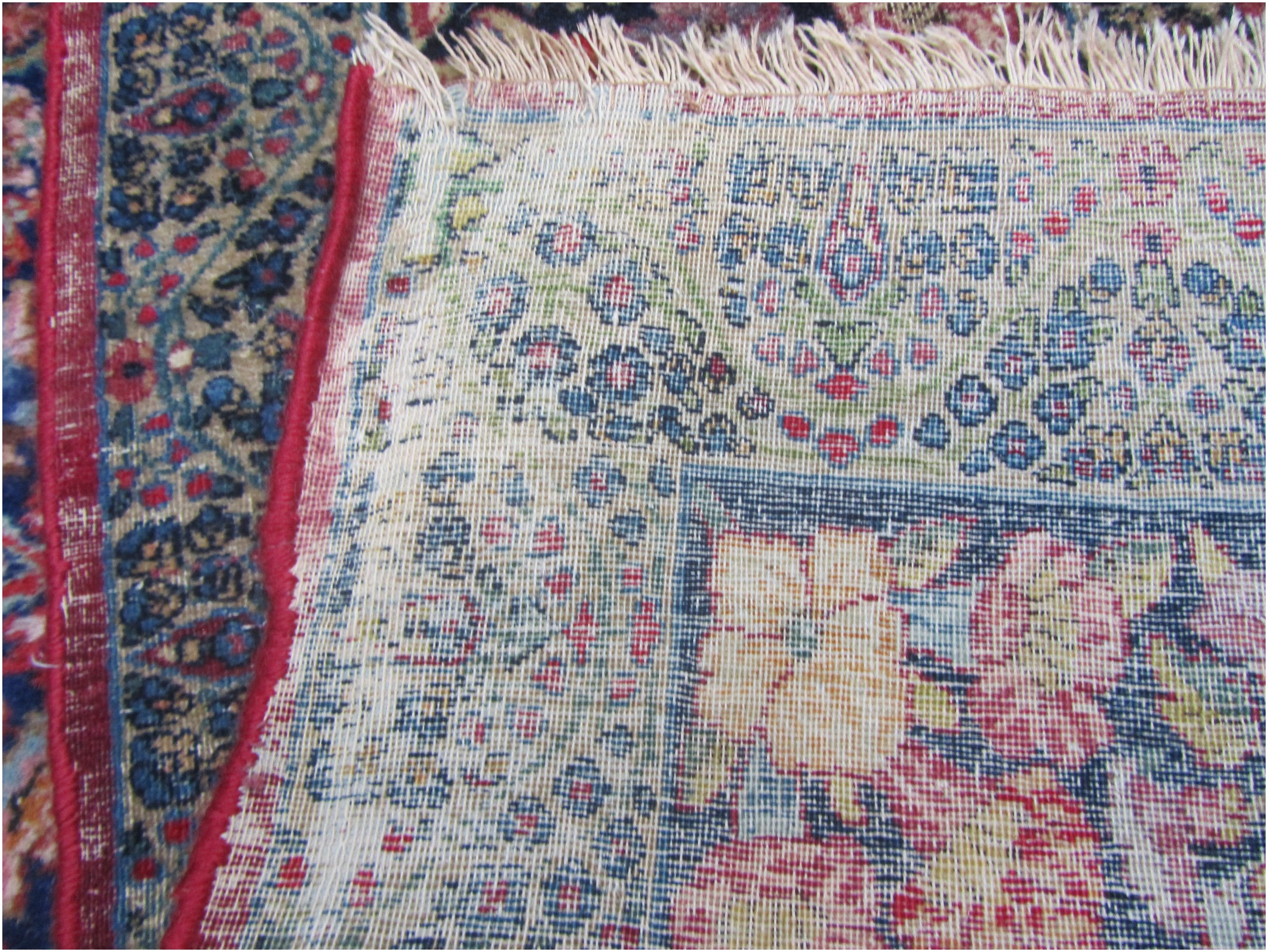 The moth damage is visible from the back of the rug.