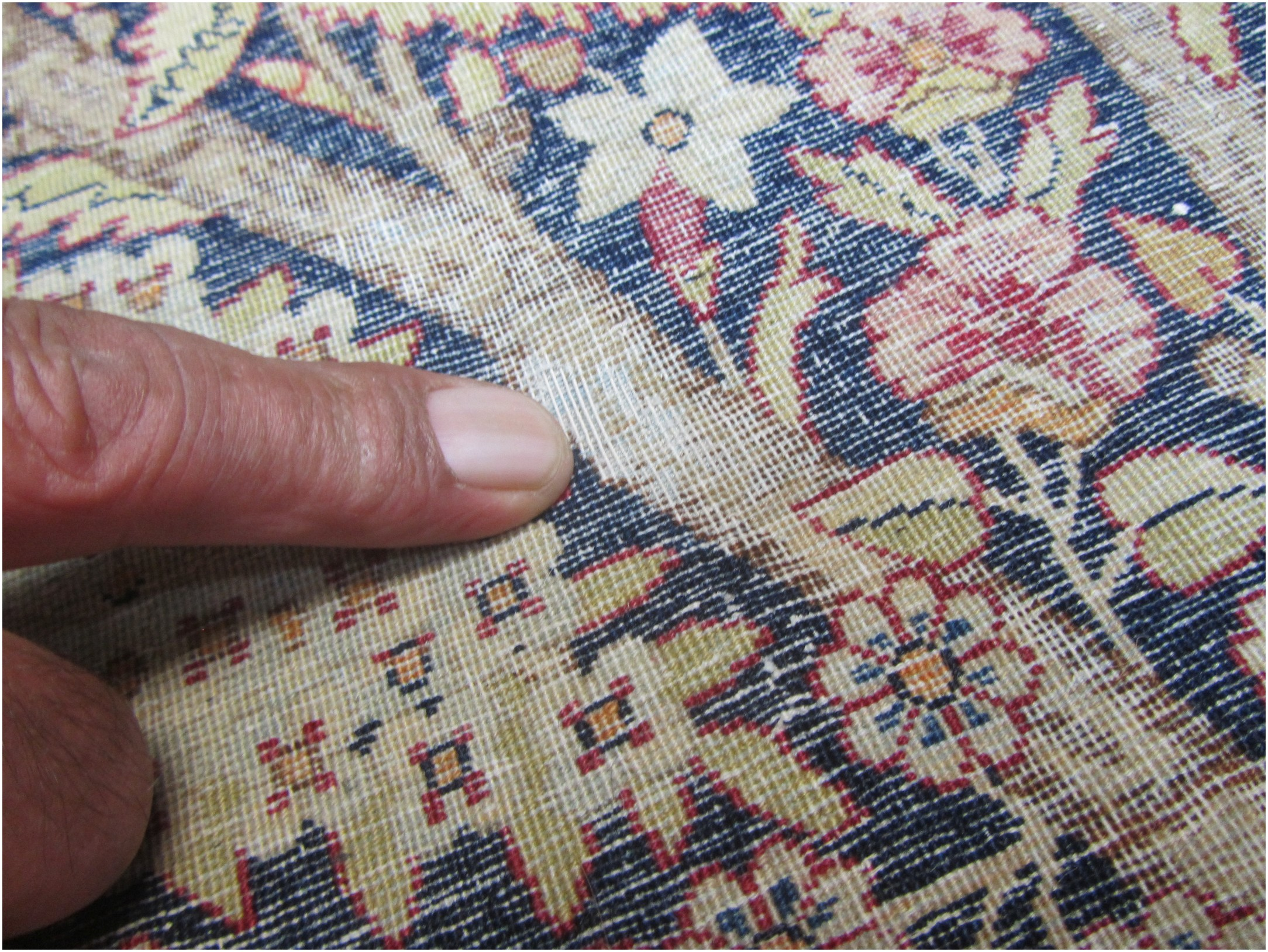 Damage is visible from the back of the rug.